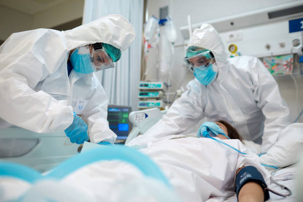 醫護人員根據COVID患者調整設備。