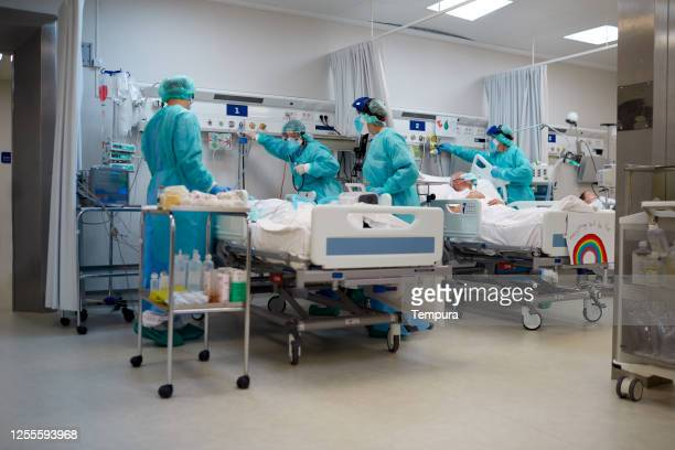 healthcare workers adjusting the oxygen supply to a covid patient. - patient on ventilator stock pictures, royalty-free photos & images
