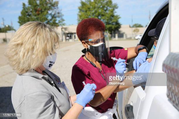 Healthcare workers administer a flu shot during a drive-thru clinic at the Louisiana State Fairgrounds in Shreveport, Louisiana, U.S., on Thursday,...