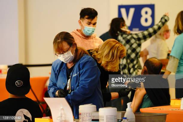 Healthcare workers administer the Pfizer-BioNTech Covid-19 vaccines at a Sharp HealthCare mass vaccination super site inside the Grossmont Center...