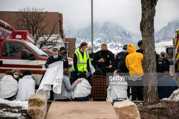 Healthcare workers and shoppers are tended to after being evacuated from a King Soopers grocery store after a gunman opened fire on March 22, 2021 in...