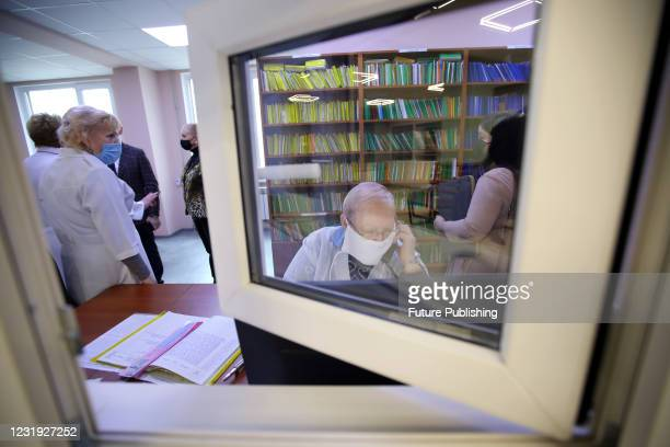Healthcare workers are seen through the window at the front desk of the Kharkiv Policlinics N20 during the COVID-19 vaccination campaign, Kharkiv,...