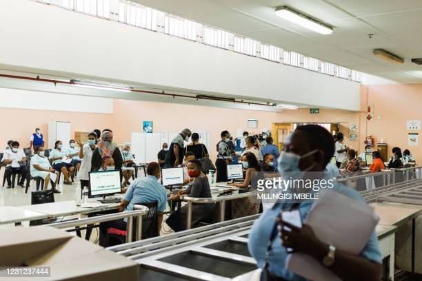Healthcare workers await to register at a vaccination site to receive a dose of the Johnson & Johnson vaccine against the COVID-19 coronavirus as...