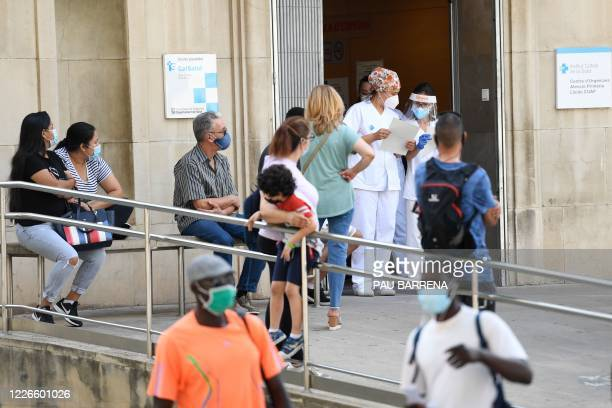 Healthcare workers check a patient´s list as people wait outside the CAP Prat de la Riba primary care centre in Lerida on July 13 2020 A local court...