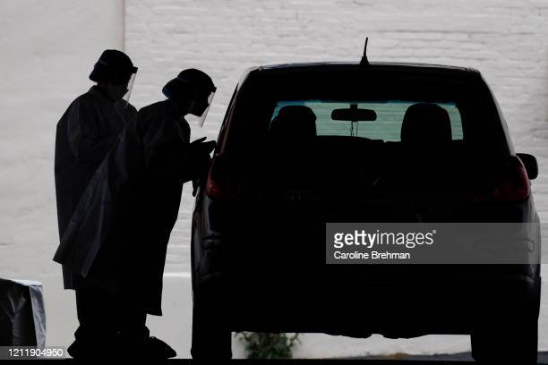 Healthcare workers conduct a COVID-19 test at a drive-thru testing facility at George Washington University on Tuesday, May 5, 2020.