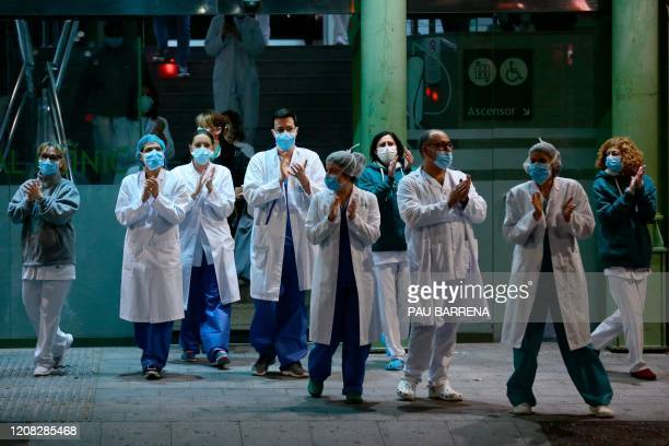 """Healthcare workers dealing with the new coronavirus crisis in Spain, applaud in return as they are cheered on by people outside """"El Clinic""""..."""