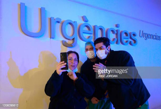 Healthcare workers dealing with the new coronavirus crisis in Spain, applaud in return as they are cheered on by people outside La Fe hospital in...
