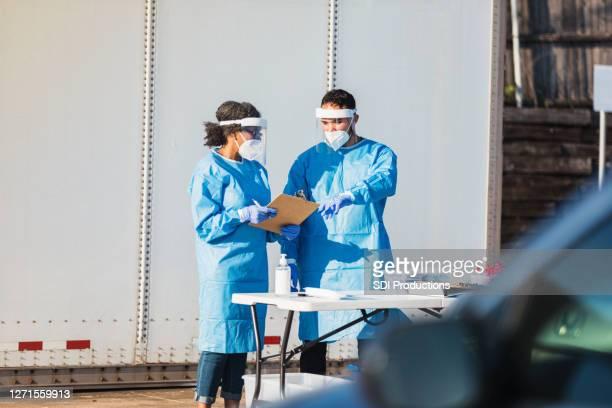 医療従事者は、ドライブスルーcovid-19テストの準備を完了します - ドライブスルー検査 ストックフォトと画像