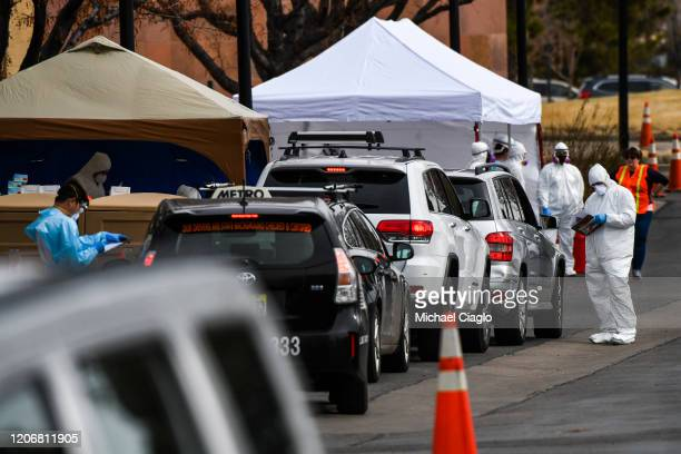 Healthcare workers from the Colorado Department of Public Health and Environment test people for COVID19 at the state's first driveup testing center...