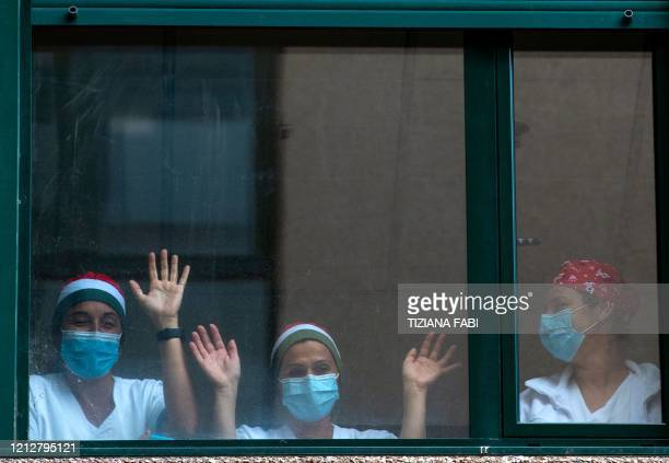 TOPSHOT Healthcare workers gesture behind windows during a performance by Italian violinist Fiamma Flavia Paolucci at Tor Vergata Hospital in Rome on...