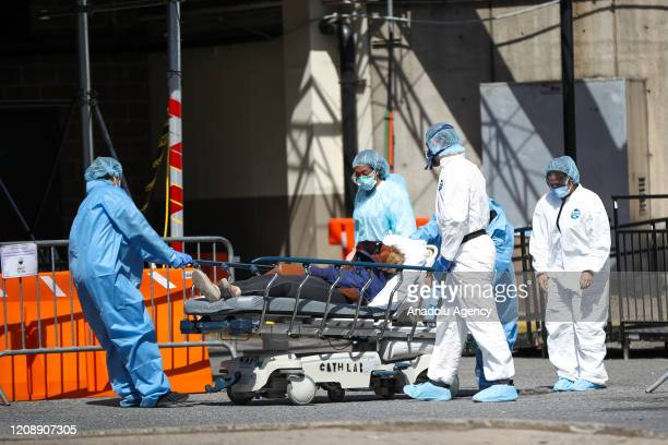 Healthcare workers help a patient who was fainted as she walked out of the Brooklyn Hospital Center in New York United States on April 1 2020 New...