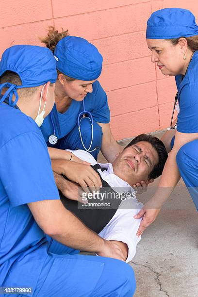 healthcare workers helping a man in trouble - epilepsy stock pictures, royalty-free photos & images