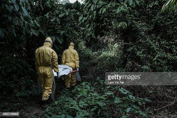 Healthcare workers in protective equipment bury a 13yearold boy dying of Lassa fever at a specific location on March 5 2014 in Bo district Sierra...