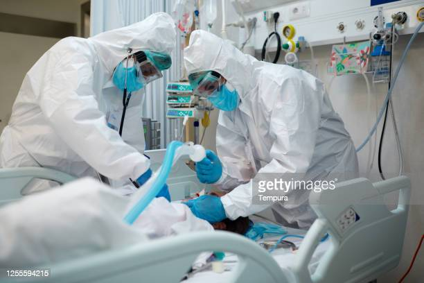 healthcare workers intubating a covid patient. - coronavirus stock pictures, royalty-free photos & images
