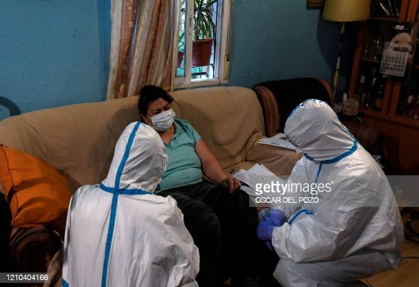 Healthcare workers of the Medical Emergency Services of Madrid UVI-6 unit, wearing protective suits, examine a suspected COVID-19 patient at her home...