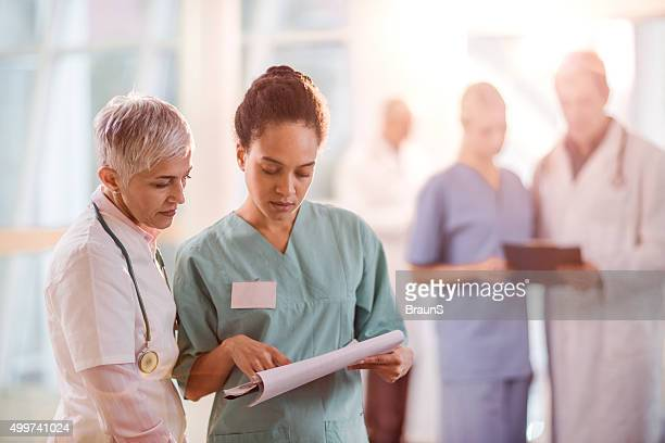 Healthcare workers reading medical documents in the hospital.