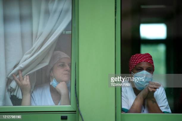 TOPSHOT Healthcare workers standing behind windows attend a performance by Italian violinist Fiamma Flavia Paolucci at Tor Vergata Hospital in Rome...