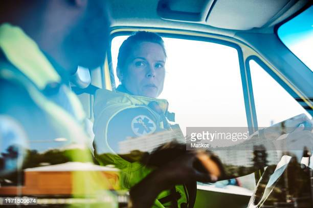 healthcare workers talking while sitting in ambulance - rescue services occupation stock pictures, royalty-free photos & images
