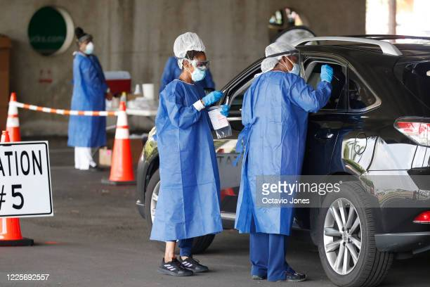 Healthcare workers test patients at the COVID-19 drive-thru testing site at the Duke Energy for the Arts Mahaffey Theater on July 8, 2020 in St....
