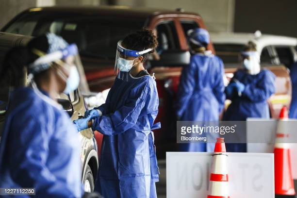 Healthcare workers test people at a Covid-19 testing site in the parking garage for the Mahaffey Theater in St. Petersburg, Florida, U.S., on...