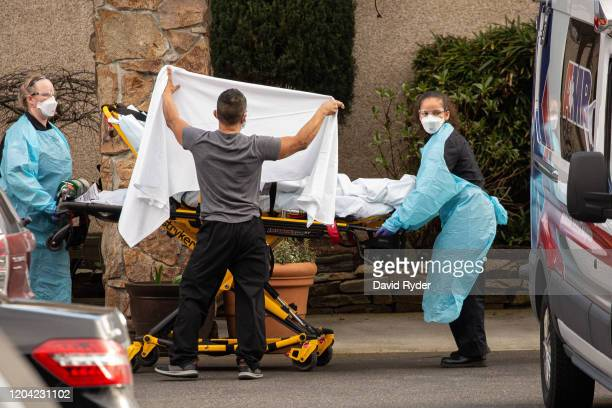 Healthcare workers transport a patient on a stretcher into an ambulance at Life Care Center of Kirkland on February 29, 2020 in Kirkland, Washington....