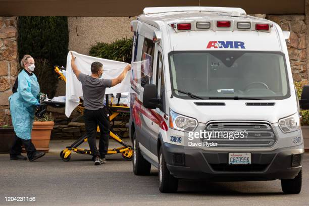 Healthcare workers transport a patient on a stretcher into an ambulance at Life Care Center of Kirkland on February 29 2020 in Kirkland Washington...