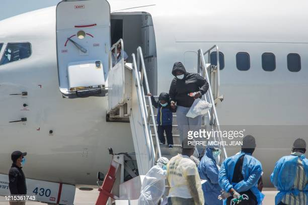Healthcare workers watch as Haitians who were deported from the United States step off a plane at the Toussaint Louverture International Airport in...