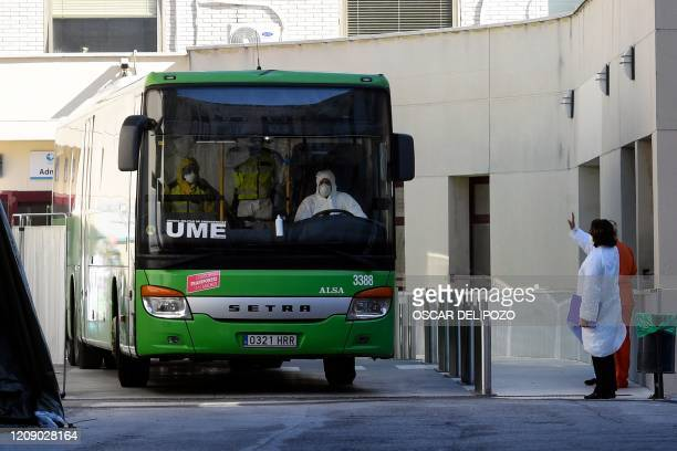 A healthcare workers waves towards a members of the Spanish Military Emergencies Unit wearing protective suits transfering patients by bus from the...