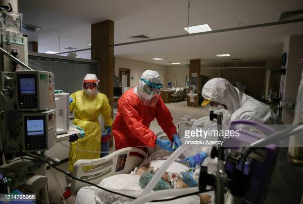 Healthcare workers wearing mask and protective suits take care of a patient at intensive care unit of Bornova Turkan Ozilhan State Hospital, turned...