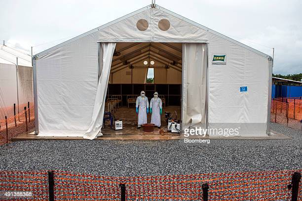 Healthcare workers wearing Personal Protective Equipment stand in a tent with patient beds at an Ebola Treatment Center in Coyah Guinea on Thursday...
