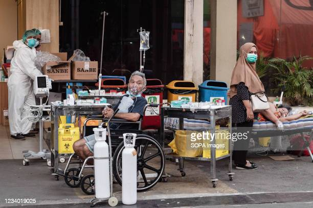 Healthcare workers wearing personal protective equipment suits are seen with COVID-19 patients having breathing difficulties outside Bekasi Public...