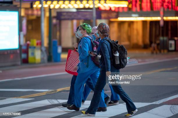 Healthcare workers wearing protective masks cross the street in Times Square amid the coronavirus pandemic on April 22 2020 in New York City United...