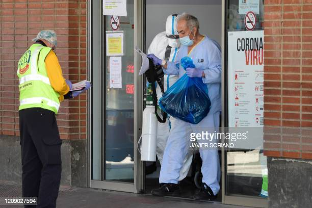 Healthcare workers wearing protective suit help a patient at the Severo Ochoa Hospital in Leganes near Madrid on April 03 before his transfert to the...
