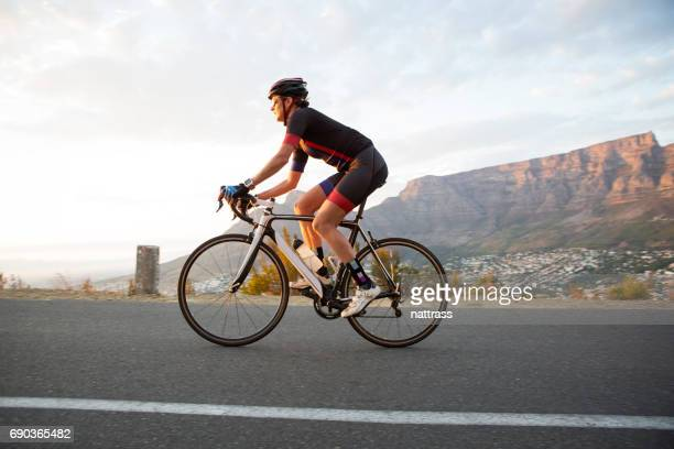 healthly female cyclist out riding early morning - racing bicycle stock pictures, royalty-free photos & images