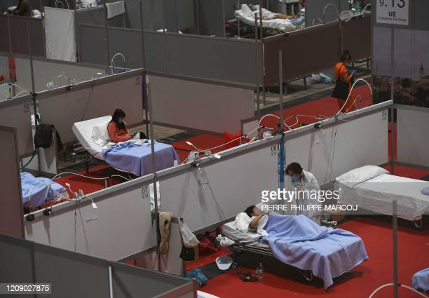 A healthworker talks to a patient at the temporary hospital for COVID19 patients located at the Ifema convention and exhibition centre in Madrid on...