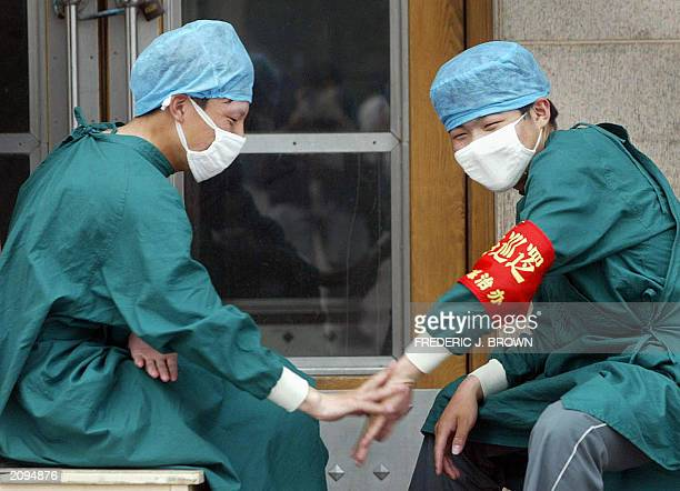 Healthworkers wearing protective masks and headgear for prevention from Severe Acute Respiratory Syndrome virus play a handslapping game while on...
