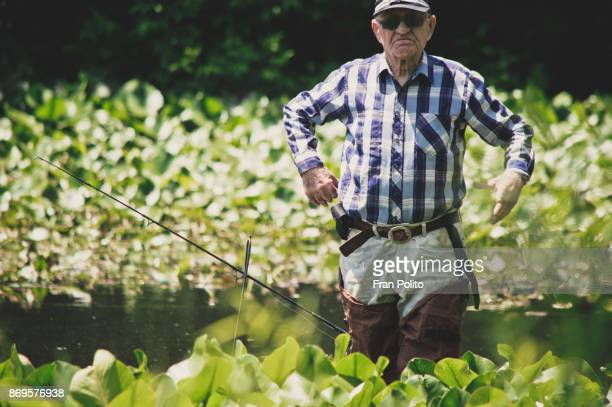 a healthy active senior man out fishing. - baldwin brothers stock pictures, royalty-free photos & images