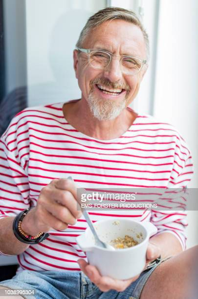 healthy and fit senior eats muesli. - sportkleidung stock-fotos und bilder