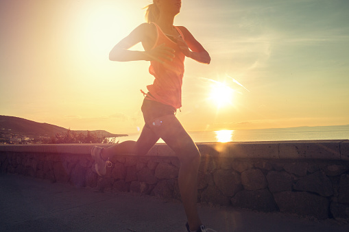 Healthy and sporty young woman running outdoors at sunset - gettyimageskorea