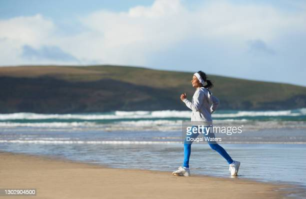 healthy asian woman exercising at beach, profile. - active lifestyle stock pictures, royalty-free photos & images