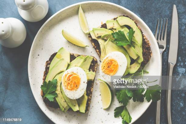 healthy avocado toasts with boiled egg on a plate - avocado toast stockfoto's en -beelden