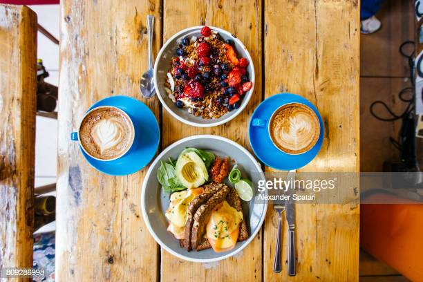 healthy breakfast for two with poached egg on salmon and rye bread and greek yoghurt with granola - the brunch stock pictures, royalty-free photos & images