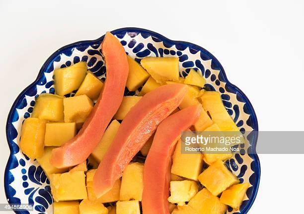 Healthy breakfast ideas Diced mango pieces along with slices of ripe papaya in a serving plate on a white background