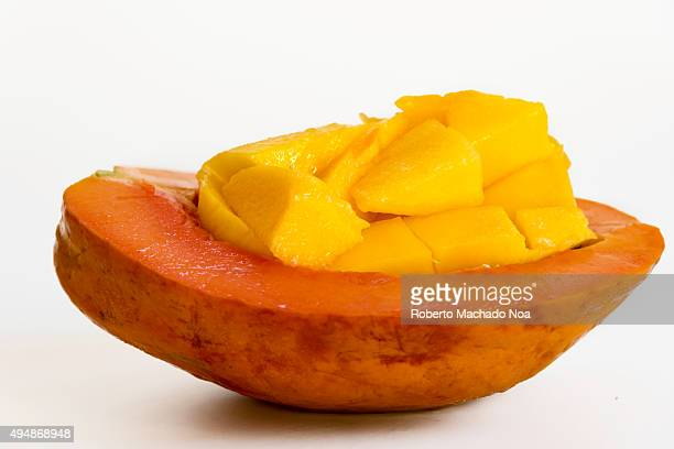 Healthy breakfast ideas Diced mango pieces placed in a half cut papaya on a white background