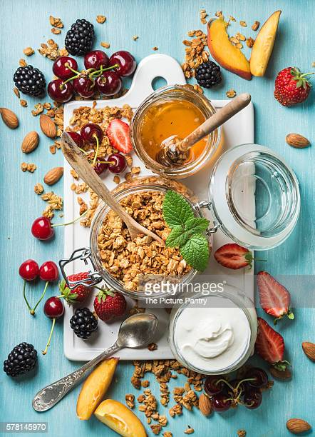 Healthy breakfast ingredients. Oat granola in open glass jar, yogurt, fruit, berries, honey and mint on white ceramic board over blue background