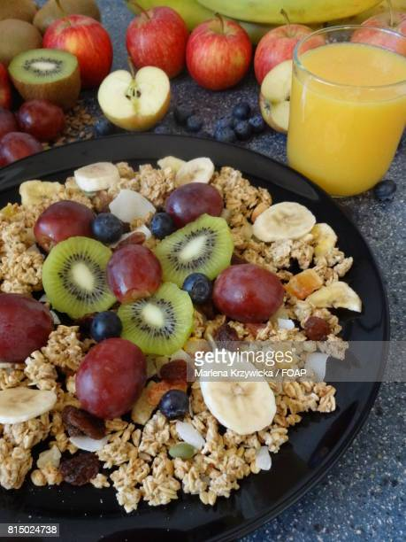 Healthy breakfast of granola with fruits and orange drink