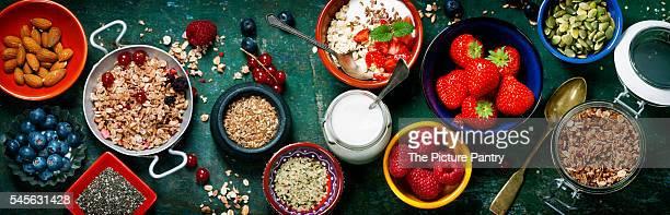 Healthy breakfast of muesli, berries with yogurt and seeds on dark background