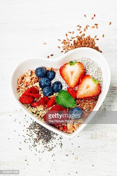 Healthy breakfast of muesli, berries with yogurt and seeds on white background