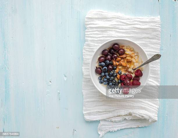 Healthy breakfast set. Bowl of oat porridge with fresh berries, almond and honey over white napkin. Top view, light blue backdrop.