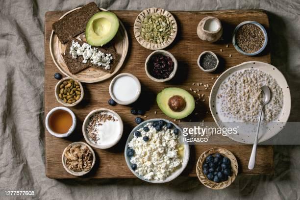 Healthy breakfast. Variety of breakfast dishes wheat. Yogurt. Kefir. Cottage cheese. Avocado. Rye bread. Seeds. Nuts and berries assortment in...